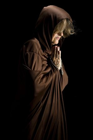 devout: Religious woman praying and holding a rosary