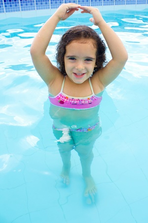 Cute and happy child in the pool as ballerina. photo