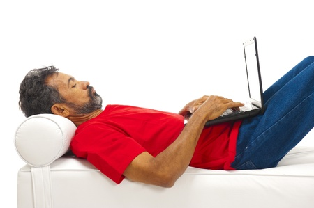 Relaxing man using laptop and lying on the sofa  photo