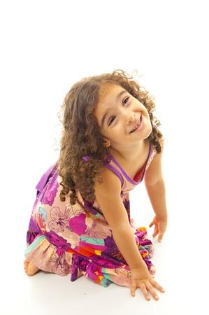 grimacing: Beautiful child smiling and kneeling grimacing.