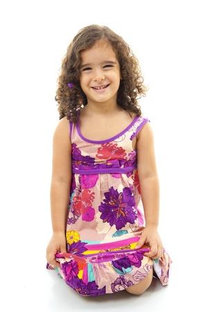 Schönes Kind, lächelnd und kniend auf weißem Hintergrund.