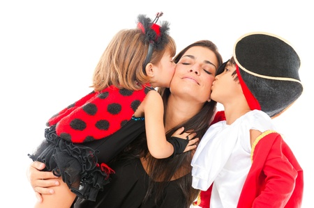 two beautiful children with costumes kissing a woman . photo