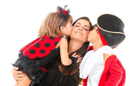 zwei schöne Kinder mit Kostümen küssen eine Frau. Lizenzfreie Bilder