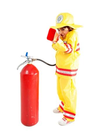 Junges Kind als Feuerwehrmann hält einen Feuerlöscher Lizenzfreie Bilder