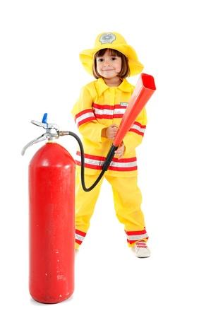 Junges Kind als Feuerwehrmann hält einen Feuerlöscher Standard-Bild - 10795548