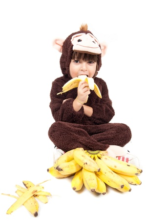 eating banana: Child with monkey costume eating banana