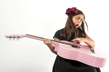 girl playing guitar: Cute young girl playing guitar and sing .