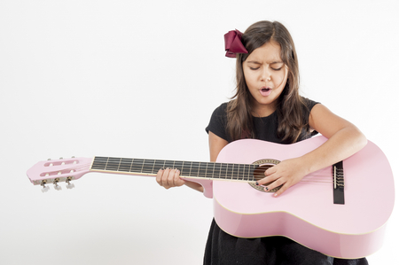 girl playing guitar: Cute young girl playing guitar and sing .