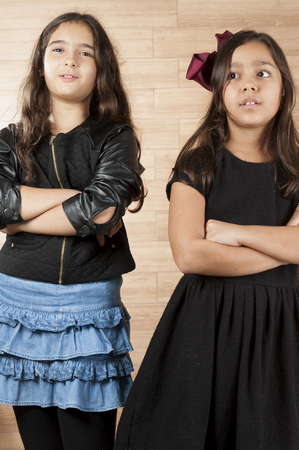 cross arms: Two cute young girls with cross arms .