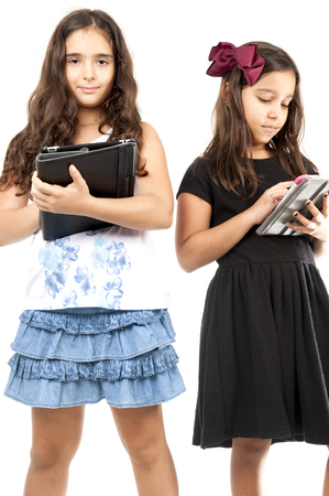 studing: Two cute young girls playing with tablet