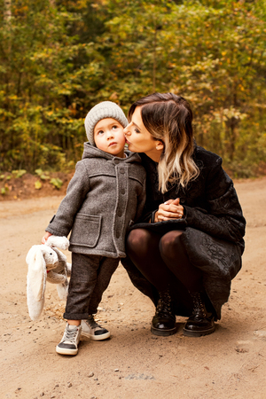 mum gently kisses her little son on the path in the woods Stock Photo