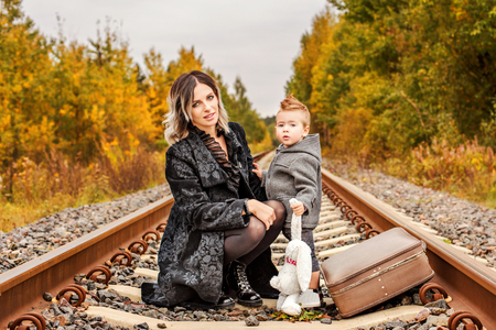 fashionable young mother with her son on the forest rails Stock Photo