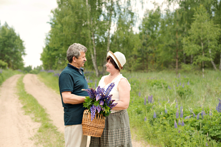 An elderly couple walks through the forest park and a man gives a woman a woven basket with a bouquet of flowers of purple lupines