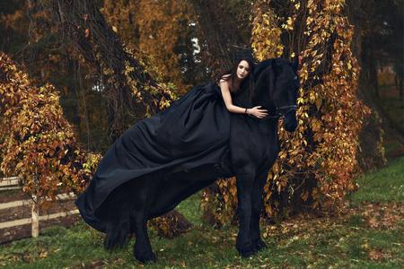 La reine veuve noire embrasse son cheval noir dans une sombre forêt