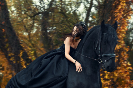 girl black queen witch in black dress and tiara riding horseback on a Friesian horse
