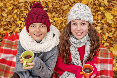 portrait of two teenagers in a cozy hat and scarf girl and boy