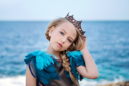 portrait of a young princess girl in a crown and azure dress is tilted her head and looks tenderly Stock Photo