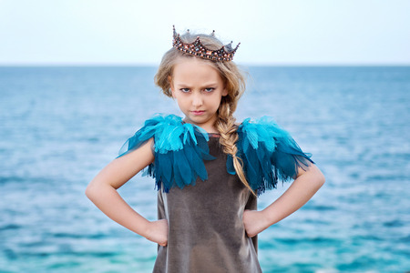 stern little princess girl in the crown watch frowningly, stands akimbo Stock Photo