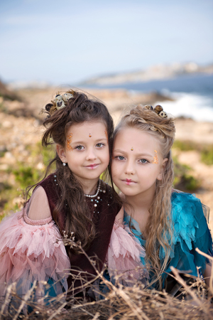portrait of two blonde girls and brunettes in fancy dresses of birds and with nests in hairstyles