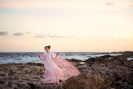 a girl in a royal crown and in a long pink dress is standing at the seashore in the rays of the rising sun and a veil is flying in the wind