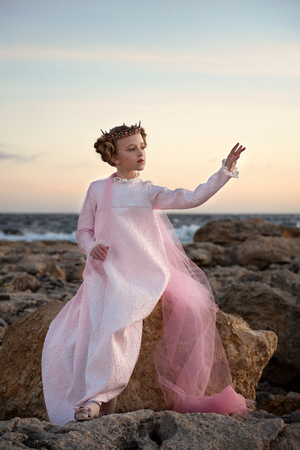 capricious princess girl sitting on a stone by the sea in a pink dress with veil and crown Archivio Fotografico