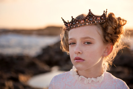 Portrait of a young capricious princess in the rays of the rising sun in the crown Stock Photo