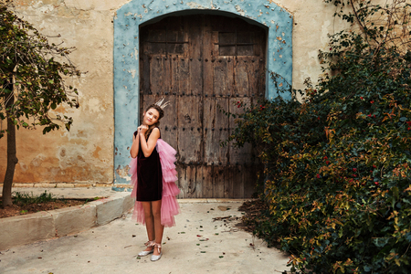 a sweet princess girl in a crown and a burgundy dress with a pink veil stands infront of an old house with an ancient wooden front door and a huge overgrown bush of a dog rose