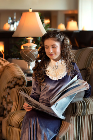maiden student in a retro dress with a jabot sits in an antique chair and reads a newspaper pensively dreams