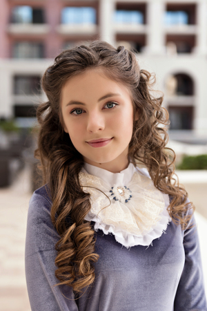 close-up portrait of a girl in retro dress and curls on building background