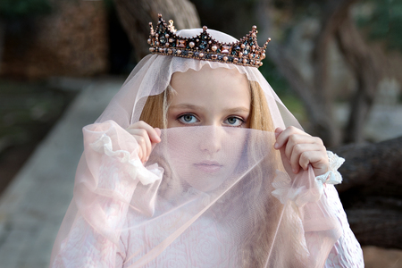a young concubine princess in the crown wraps her face with a veil and looks reproachfully