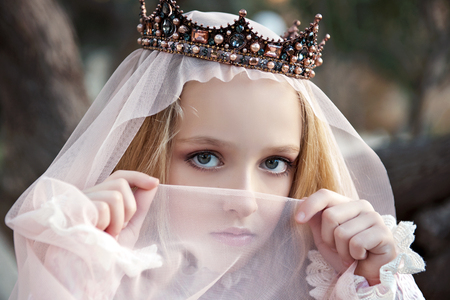 close-up portrait of the girl enchantress in the crown with a face covered with veil and charming big eyes