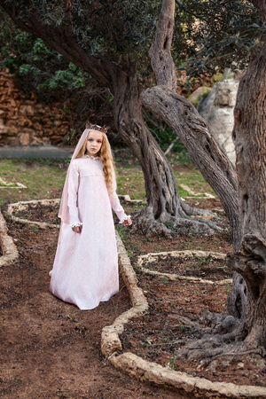 a little princess of spirits and fairies standing in the enchanted mysterious magic in a wedding dress with a veil and crown Stock Photo