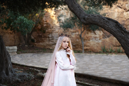 beautiful white witch foreteller stands in a mysterious magical forest in a wedding dress with a veil and crown