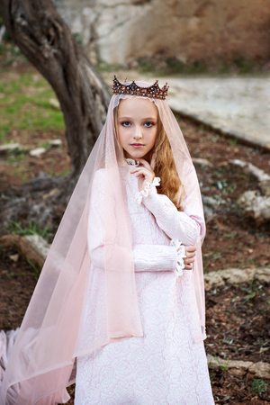dolly princess of the fairy elves stands in a magical enchanted forest and enchantly looks