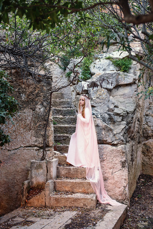 a young white witch queen climbs the stone steps of a fairy-tale staircase in a long dress and a diadem with a veil Stock Photo