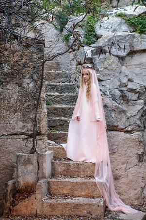 Young white pixie queen in a crown with a veil and a long dress down the stone stairs in a fabulous location Stock Photo