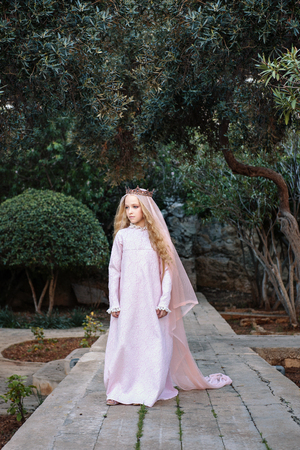 fairy-tale kind white sorceress in a magical forest walks along the path in a dress and a crown with a veil