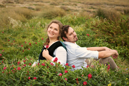 a rustic loving couple gently peacefully gossiping sits back to back in the bushes with flowers in old-fashioned retro clothes