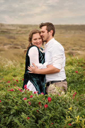 a married couple gently lovingly hugs in the briars of roses on a background of a stormy sky in vintage rustic retro clothes Stockfoto - 100480246