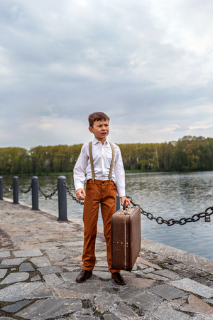 little boy simpleton in an old-fashioned rustic clothes with a vintage suitcase standing at the arrival station on the pier of the lake Stock Photo