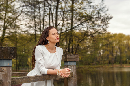 dreaming pensive young woman standing leaning on a railing of a wooden bridge in a white dress looking forward