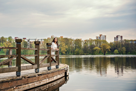 thinking woman in white dress is standing on a wooden pontoon bridge on a river lake with a cityscape on a background
