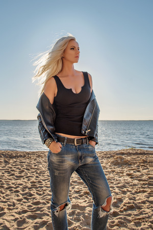 a portrait of a daring blonde girl in a tight-fitting t-shirt and torn jeans standing on the sandy beach of the sea and looking thoughtfully