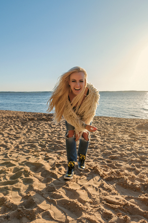 pretty blond girl in a youth lifestyle suit on the beach laughing loudly and smiling