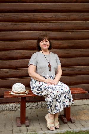 portrait of an elderly woman in a gray linen dress sitting on a wooden bench near a log house in the village Reklamní fotografie