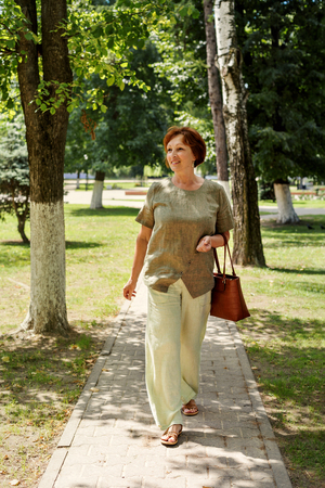 a woman wearing a vigorously worn walks along a path in a park dressed in linen clothes and flying hair