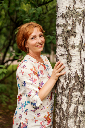 portrait of a middle-aged woman tranquil woman hugging a birch Stock Photo