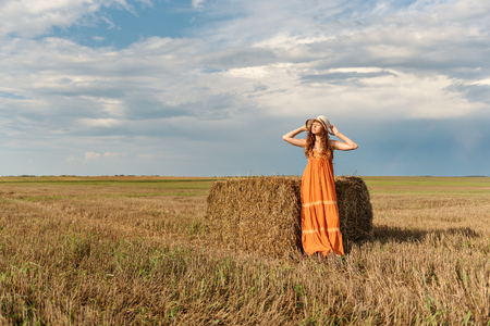 a young attractive curly rural woman in a retro vintage dress and a hat stretching stands near a stack of harvested wheat