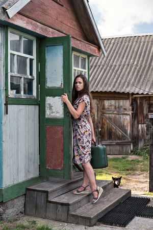 a rural young teacher with a suitcase walks through the doors of an old, shabby village school in the countryside