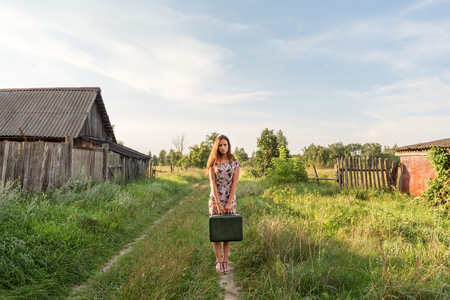 a model girl in a retro dress is holding in her hands a vintage suitcase on an abandoned country road overgrown with grass between the village courtyards and huts